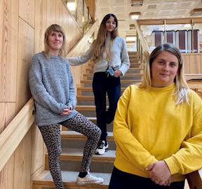 Bild på Karolina, Petra och Sara som jobbar på biblioteket. De står i trappan på Falu stadsbibliotek