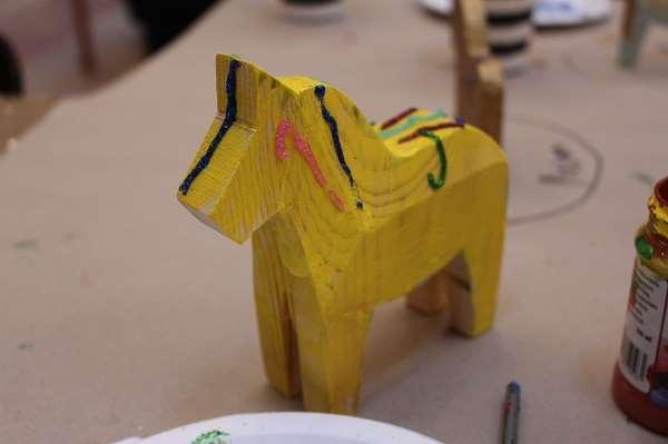 En gulmålad dalahäst med glitter på.