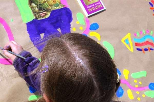 Bild av en flicka som målar på ett stort papper.