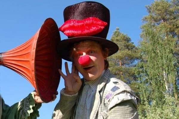 Man utklädd till clown lyssnar med örat tätt intill en stor grammofontratt.
