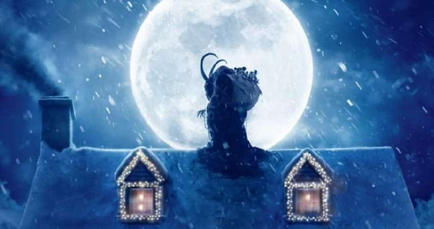 Krampus framför en fullmåne på ett snötäckt hustak.