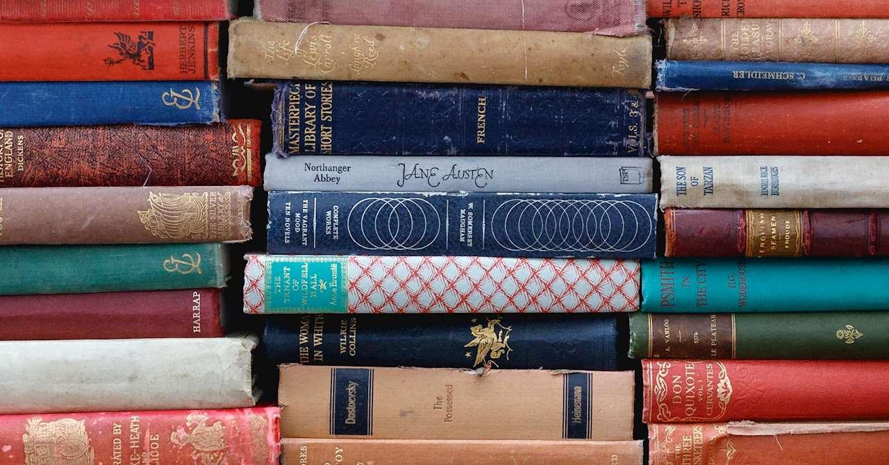 Böcker med omslag i olika färgar staplade på varandra i tre staplar