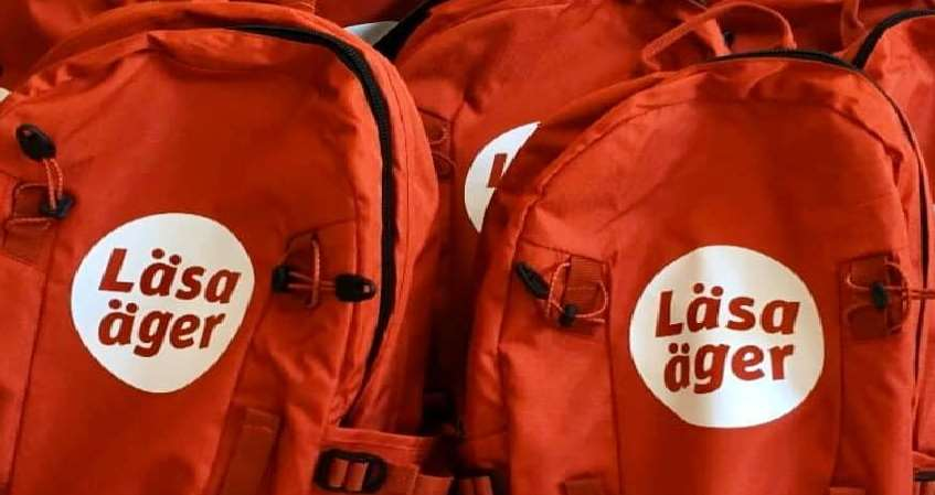 Ett gäng lysande röda ryggsäckar med texten Läsa äger i rött på vitt