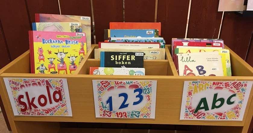 Ett boktråg av trä med bilderböcker om att börja skolan och att lära sig läsa och räkna